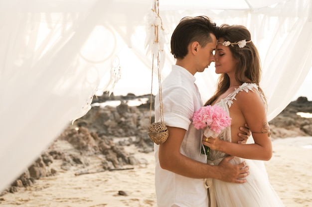 Happy married couple is celebrating their wedding on the beach at tropical island
