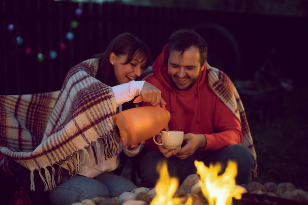 A happy married couple is drinking tea from a teapot outdoors by the fire