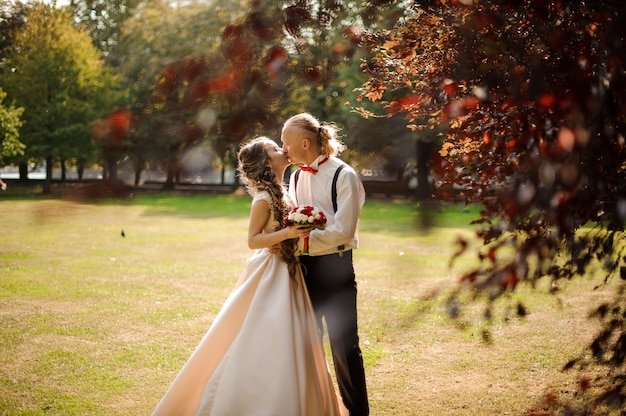 Happy married couple kissing on a green grass field with a tree in a foreground