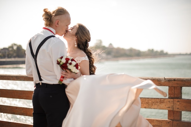 바다와 하늘의 배경에 나무 다리에 키스 행복 한 결혼 커플