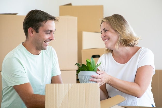 Happy married couple moving into new flat, unpacking things, sitting on floor and taking houseplant from open boxes