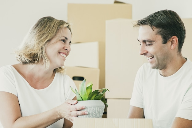 Felice coppia sposata che si trasferisce nel nuovo appartamento, disimballare le cose, sedersi sul pavimento e prendere la pianta d'appartamento da scatole aperte