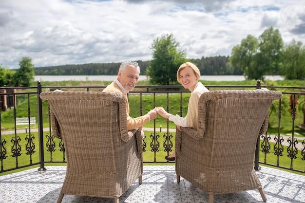 Счастливая супружеская пара позирует на фоне живописного пейзажа