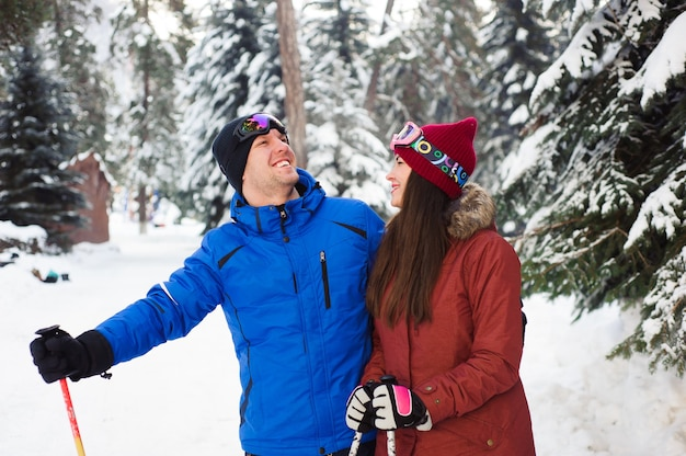 森の中のスキーリゾートでスキーをする幸せな夫婦