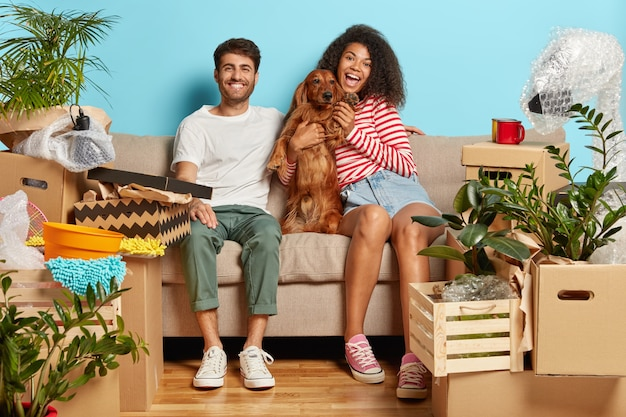 Happy married couple on sofa with dog surrounded with cardboard boxes