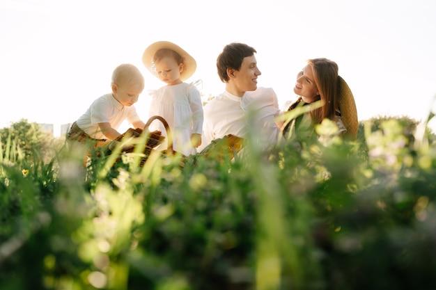 子供と幸せな夫婦は、フィールドの緑の牧草地に座っています子供たちはバスケットから食べ物を取得します