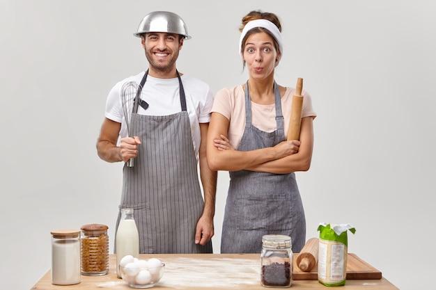 Счастливая семейная семейная пара соревнуется в кулинарии, готовит вкусную еду, стоит рядом друг с другом, одевается в фартуки, держит в руках кухонные принадлежности, веселится, готовя выпечку. концепция приготовления пищи