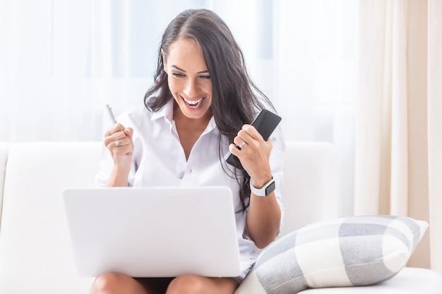 Счастливая замужняя дама празднует новости, которые она читает со своего компьютера, поставленного на колени, сидя на диване в своей гостиной, с победным жестом кулака держит мобильный телефон и ручку.