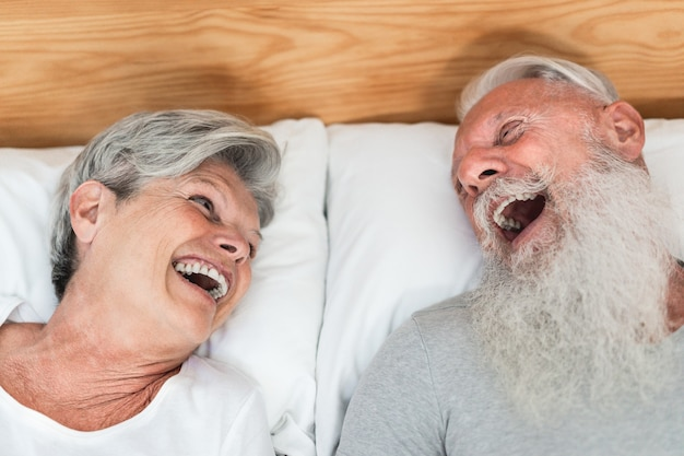 Happy married senior couple having fun lying in bed - main focus on woman face