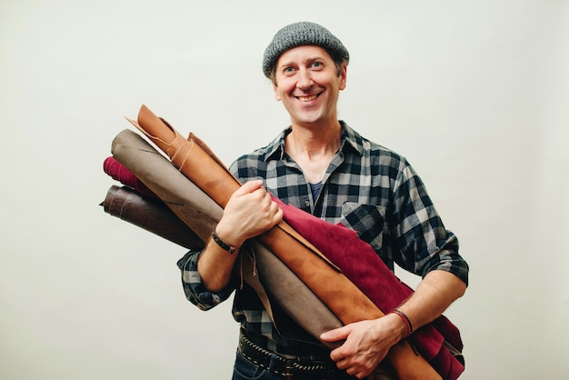 Happy master has idea for new leather products. tailor with rolls of lether. small business and entrepreneur concept. artisan in plaid shirt, holds set of leather in his workshop