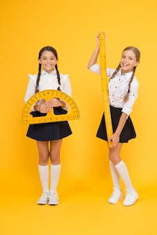 Happy math. stem disciplines. back to school. maths and geometry. kids in uniform at yellow wall. friendship and sisterhood. happy small girls study mathematics. students use protractor ruler.