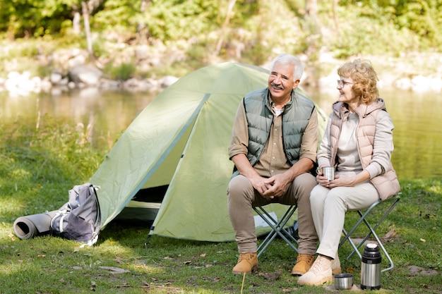 テントで観光客の椅子に座ってお茶を飲みながら、旅行の瞬間を話し合う幸せな成熟したアクティブな配偶者