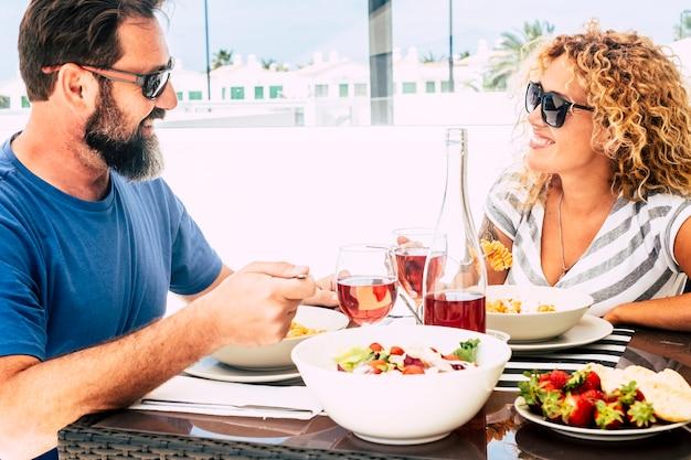 幸せな成熟した大人のカップルは一緒に昼食を楽しんでいます
