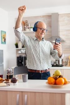 朝食時にキッチンでヘッドフォンを着用して音楽を聴いて幸せな成熟した大人。現代の楽しい幸せなライフスタイルを楽しんで、リラックスして踊り、笑顔で、現代の技術を使用して高齢者の退職者