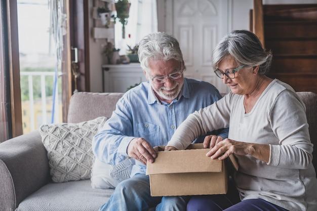 행복한 성숙한 나이든 가족 커플은 판지 상자를 풀고 인터넷 상점 구매 또는 예상치 못한 선물에 만족하고 빠른 배송 서비스, 긍정적인 쇼핑 경험에 흥분합니다.