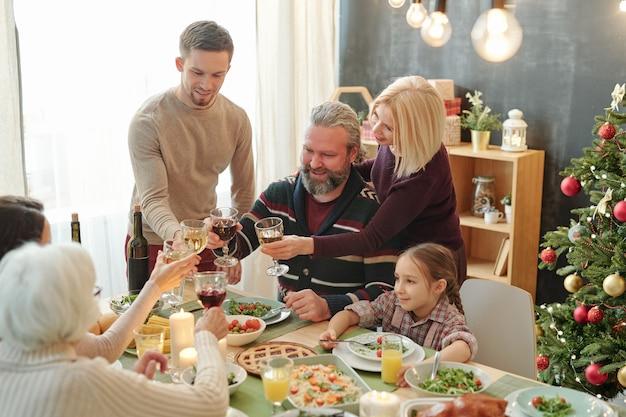 Счастливые зрелые и молодые пары, тосты с бокалами вина за домашней едой на праздничном столе во время рождественского ужина