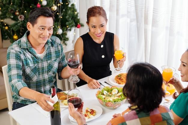 家で友達と新年の夕食を楽しんで幸せな成熟したアジアのカップル