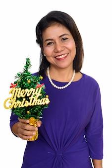 흰 벽에 고립 된 메리 크리스마스 트리를 들고 행복 성숙한 아시아 여자