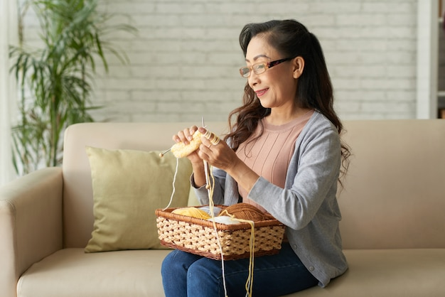 Happy mature asian woman knitting clothes sitting on sofa at home