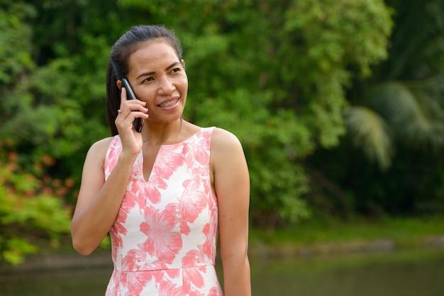 屋外の公園で電話で話している幸せな成熟したアジアの女性