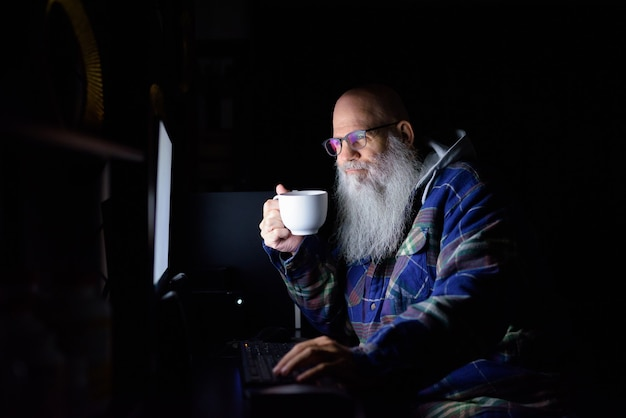 Happy mature bald bearded hipster man drinking coffee while working overtime at home late at night