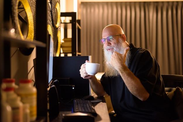 Счастливый зрелый лысый бородатый мужчина пьет кофе во время видеозвонка на работе из дома поздно ночью
