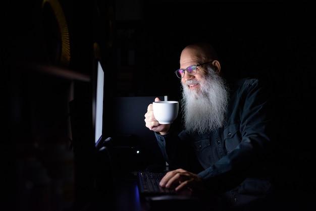어둠 속에서 집에서 초과 근무를하는 동안 커피를 마시는 행복 성숙한 대머리 수염 남자