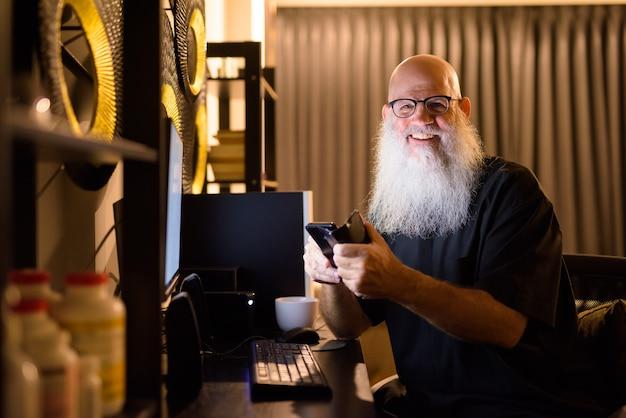 夜遅くまで家で残業しながら電話を使用して幸せな成熟したハゲのひげを生やした男