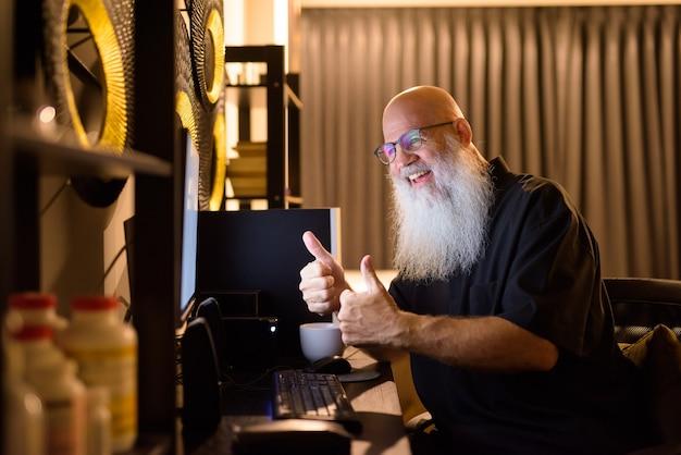 Счастливый зрелый лысый бородатый мужчина видеозвонок на работе из дома поздно ночью