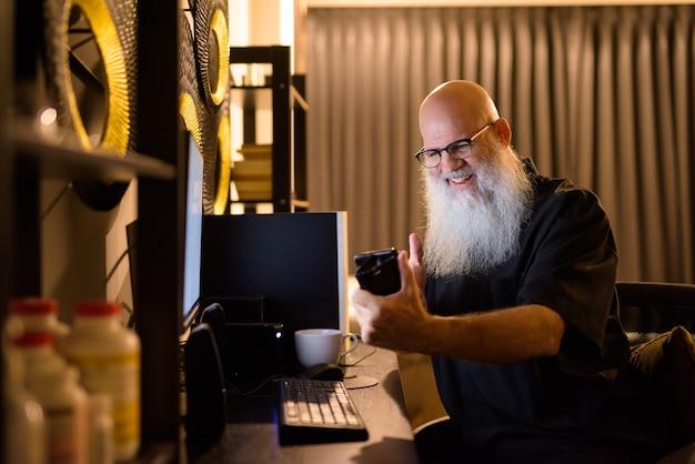 Счастливый зрелый лысый бородатый мужчина видеозвонок во время сверхурочной работы дома поздно ночью