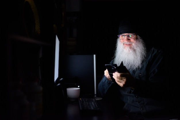 Happy mature bearded hipster man using phone while working overtime at home in the dark