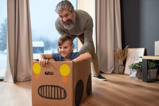 Happy mature bearded man in casualwear pushing cardboard box with his grandson while both having fun during play in living-room