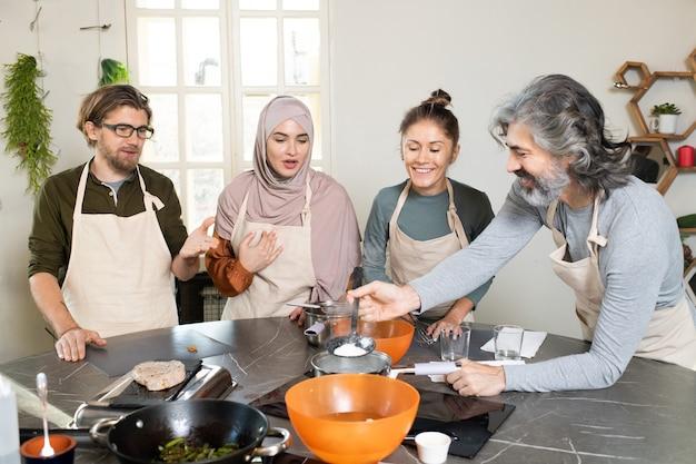 マスタークラスの学習者の間でテーブルで調理しながら沸騰したお湯で金属鍋の上にキッチンツールを保持している幸せな成熟したひげを生やした男
