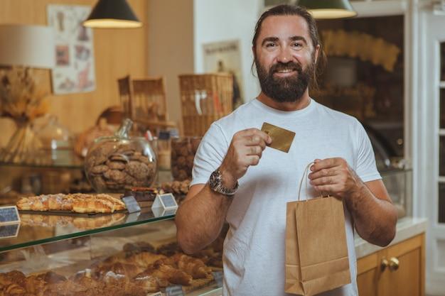 Счастливый зрелый бородатый мужчина держит сумку и кредитную карту, радостно улыбаясь в пекарне