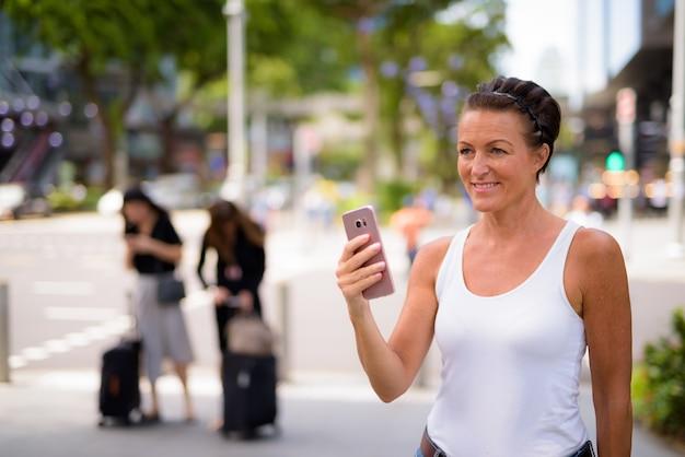 屋外の街の通りで電話を使用しながら考えている幸せな成熟した美しい観光客の女性