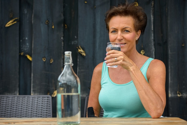 Happy mature beautiful woman drinking water at restaurant outdoors