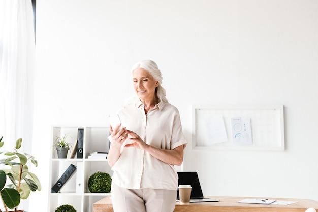 Счастливая зрелая бизнес-леди, держащая мобильный телефон