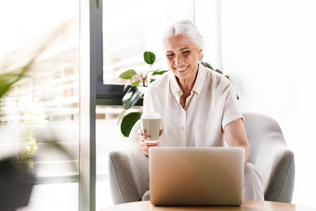 Happy mature business woman working on laptop computer