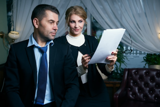 Happy mature businessman and businesswoman working with documents
