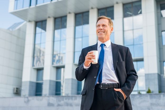 Happy mature businessman holding cup of coffee