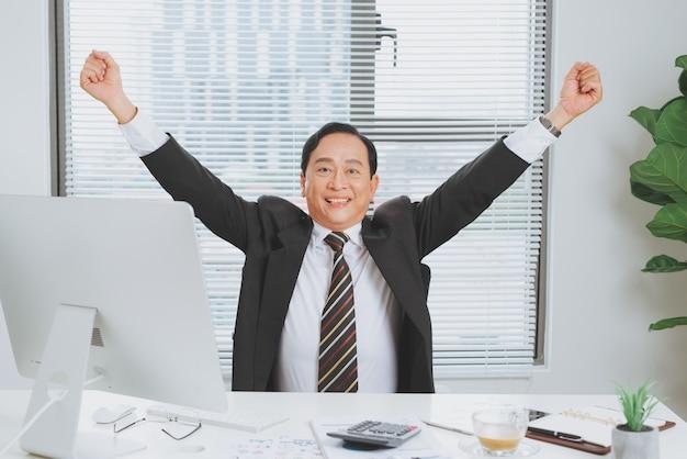 믿을 수 없는 비즈니스 성공을 축하하는 소송에서 행복한 성숙한 사업가가 손을 들고 있습니다.