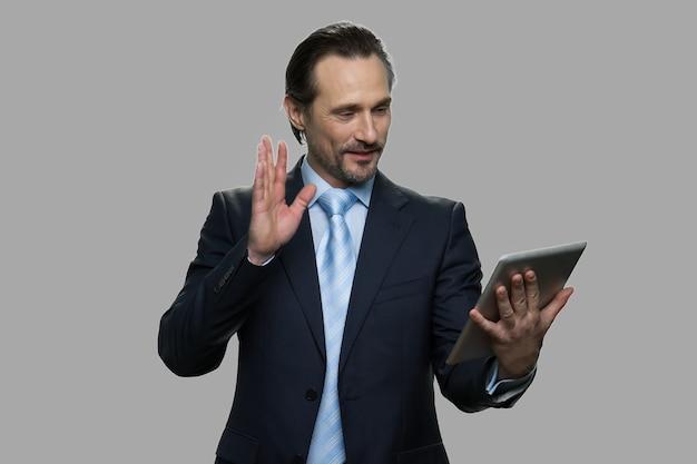 ビデオ通話を持っているスーツの幸せな成熟したビジネスマン。灰色の背景にタブレットコンピューターを保持しながら彼の友人に手で手を振っている陽気なビジネスマン。