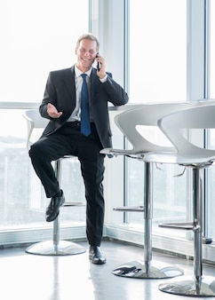 Happy mature businessman sitting on stool talking on cellphone