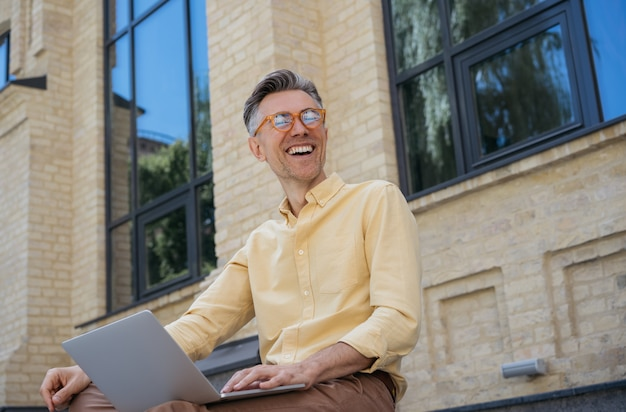 Happy mature businessman using laptop, typing on keyboard, laughing