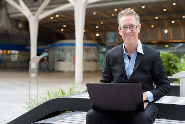 Happy mature businessman using laptop while sitting in the city outdoors