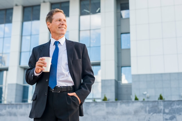 Happy mature businessman with cup of coffee in front of building