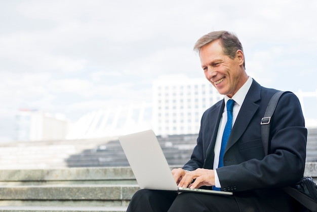 Happy mature businessman working on laptop at outdoors