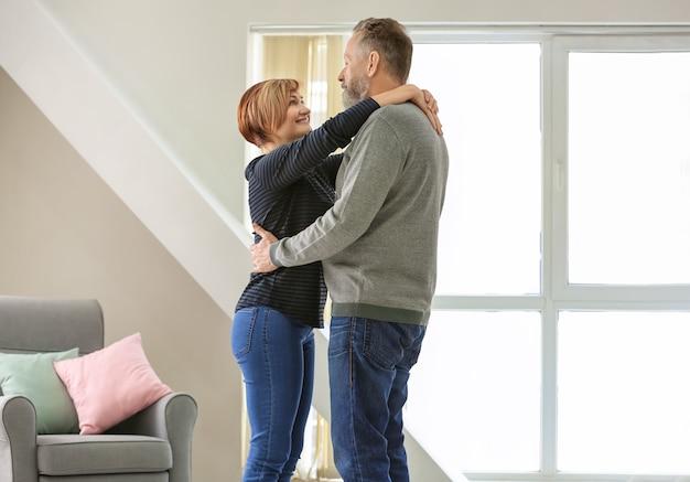 Счастливая зрелая пара танцует дома