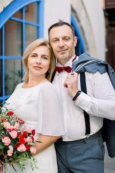 幸せな成熟したカップル、街の屋外で抱き締め、美しいヴィンテージの青い窓の近くでポーズをとる