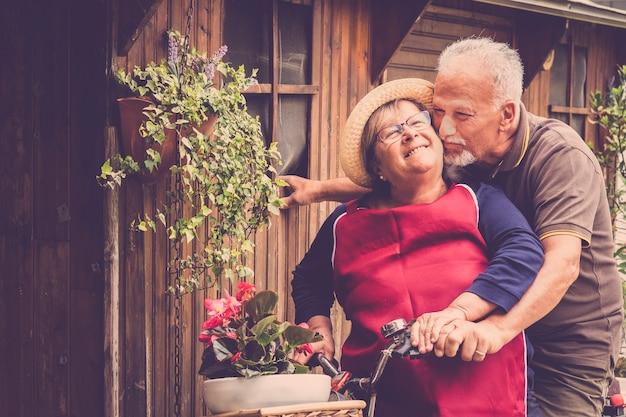 愛の幸せな成熟したカップルは、楽しんでキスをして屋外の自転車に一緒に滞在します。